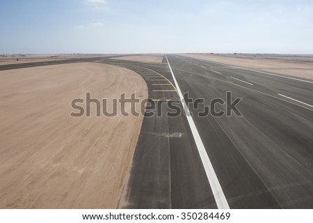 Aerial panoramic view of a commercial airport runway with connections and taxiways - stock photo