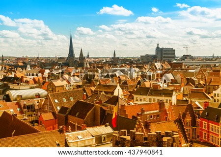 Aerial panoramic view of Ghent, Belgium with  roofs and traditional medieval buildings, church tower against cloudy blue sky - stock photo