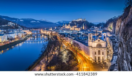 Aerial panoramic view of the famous historic city of Salzburg with Hohensalzburg Fortress and Salzach river in twilight during blue hour at dusk, Salzburger Land, Austria - stock photo