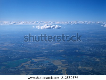 Aerial photo of land and clouds from above. - stock photo