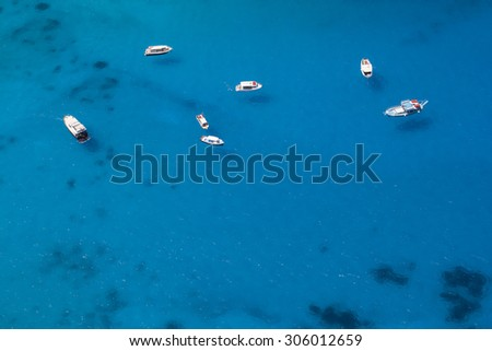 Aerial photo of several boats anchored in a sea bay with shallow clear blue water. The water is clean enough to enable to see the boats shadows on the seabed.