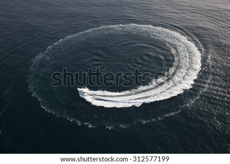 Aerial photo of small yacht making a turn in form of a circle in the water on a beautiful sunny day