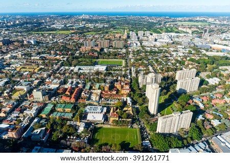 Aerial photo of typical Sydney neighbourhood suburb. Residential buildings with office skyscrapers among green parks and sport fields - modern urban infrastructure  - stock photo