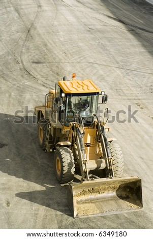 aerial pic of a bulldozer or front loader used in freeway or road construction. - stock photo