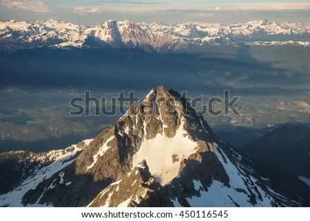 Aerial Picture of a Beautiful Mountain Peak near Squamish, BC, Canada. Taken during a hazy sunset. - stock photo
