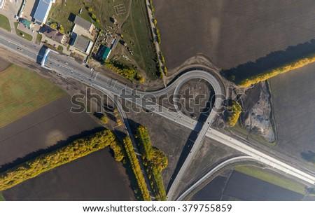 Aerial road interchange, viaduct. Crossroads view parking lots, bridges. Copter shot. Panoramic image. - stock photo