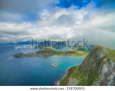 Aerial scenic view of peaks on Lofoten islands covered by scattered clouds - stock photo