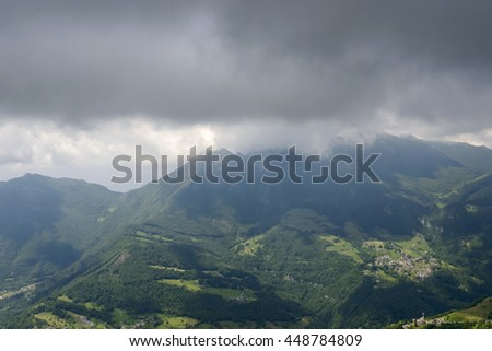 aerial shot, from a small plane, of Brumano village in Imagna valley , shot with Resegone range covered with dark clouds in Orobie mountains, Bergamo, Lombardy , Italy