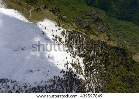 aerial shot, from a small plane, of the slopes of Arera peak range with recent springtime snow, shot in Orobie mountains, Bergamo , Italy - stock photo