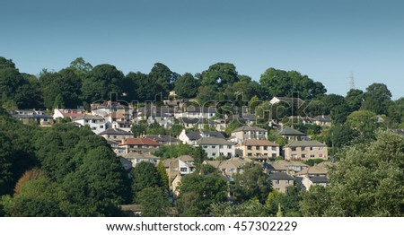 Aerial shot looking across to hillside urban housing development - housing estate of mainly semi detached homes in Yorkshire England UK nestled in green trees against blue sky - stock photo