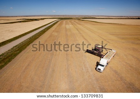 Aerial shot of a combine emptier a hopper into a semi truck on the prairie - stock photo