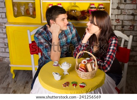 Aerial Shot of Young Couple in Checkered Tops, Looking Each Other with Hands on their Faces While Dating at the Cafe Shop - stock photo