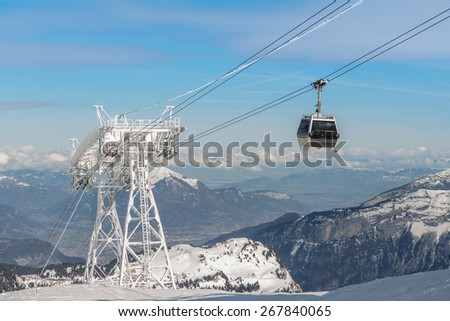 aerial ski lift arrival on french alps background - stock photo