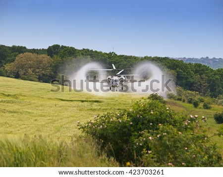 Aerial spraying over a field of wheat  - stock photo