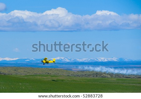Aerial top dresser agricultural aircraft spraying fertilizer over green field - stock photo