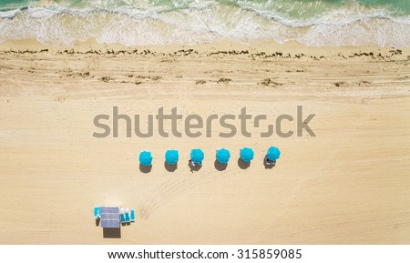 Aerial top view on the Miami beach. Umbrellas, sand and ocean. - stock photo