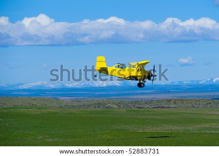 Aerial topdresser agricultural aircraft spraying fertilizer over green field - stock photo