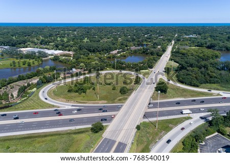 Aerial view a highway and ramp near a nature area with Lake Michigan in the distance in suburban Chicago.