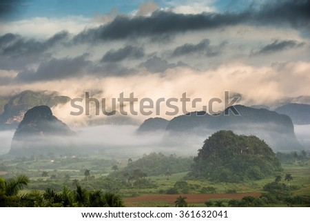 Aerial View across the Vinales Valley in Cuba. Morning twilight and fog. Fog at dawn in the Valley of Vinales in Pinar del Rio, famous for tobacco plantations in Cuba, world heritage site of Unesco  - stock photo