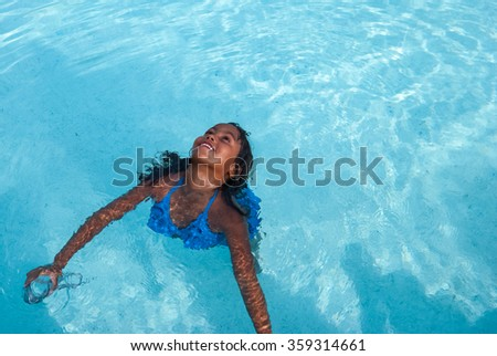 Aerial view at beautiful brazilian girl wearing blue swimsuit with diving goggles  Smiling female child swimming in a pool with clear water on a sunny day - stock photo