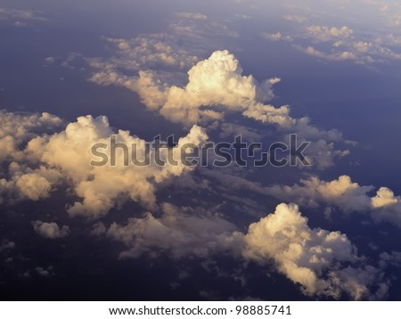 Aerial view at sunset: Tops of cumulus clouds seen from 30,000 feet or higher over land - stock photo