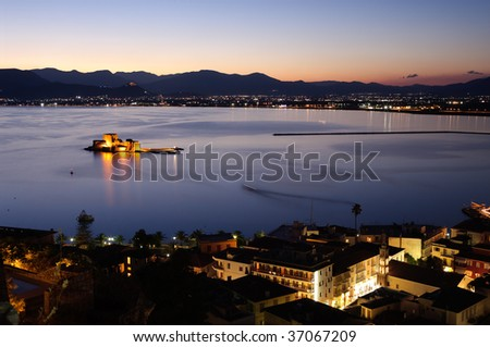 aerial view by night of bay Nauplia at twilight with the castle of Bourtzi on the small island - stock photo
