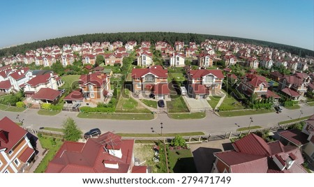 Aerial view car rides by road in cottage town at sunny summer day. - stock photo