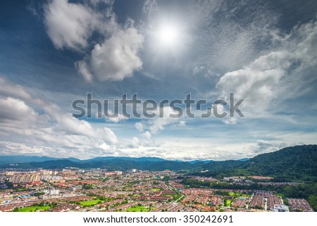 Aerial view cityscape and mountains against blue cloudy sky and bright sun - stock photo