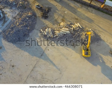 Aerial view construction site with rubble and scrap remaining after derelict building demolition. Hydraulic backhoe bulldozer removes crumbling demolished debris, brick, stone and concrete for recycle
