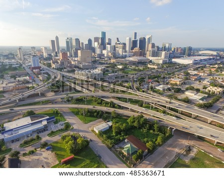 Aerial view downtown and interstate 45 and 69 highway intersection, massive intersection, stack interchange and elevated road junction overpass at sunset from the southeast side of Houston, Texas, USA