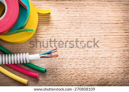 aerial view electric cable in corrugated pipe rolls of isulating tape heat shrinkable tubes on wooden board  - stock photo