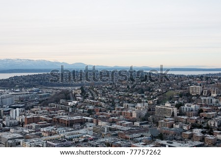 Aerial view Elliot Bay on Puget Sound, overlooking the city skyline of Seattle Washington with mountain ranges on distant horizon - stock photo