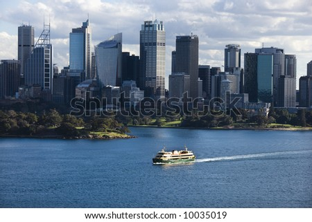 Aerial view ferryboat crossing harbour with skyline of Sydney, Australia.