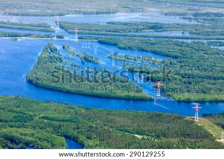 Aerial view flooded forest plains with country road and power lines. - stock photo