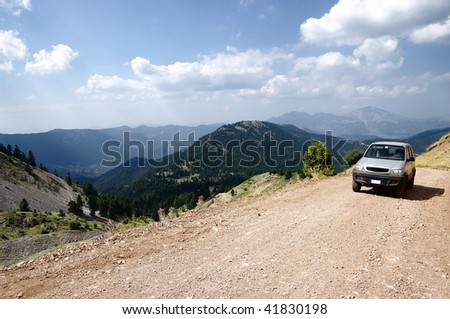 aerial view for vehicle off-road on dirty road of greek mountain - stock photo