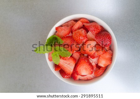 Aerial view fresh aromatic red strawberries cutted in thin slices  Healthy fruits in white bowl with green mint leaves on metallic silver background - stock photo