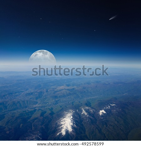 Aerial view from high altitude of mountains with snowy peaks. Full moon rises over horizon, comet and stars in dark blue space. Elements of this image (only moon) furnished by NASA