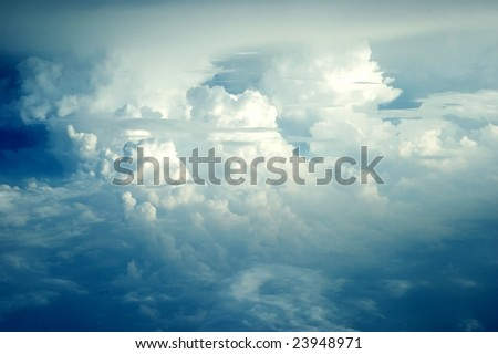 Aerial view from passanger's plane, many clouds covering sky somewhere above China. - stock photo