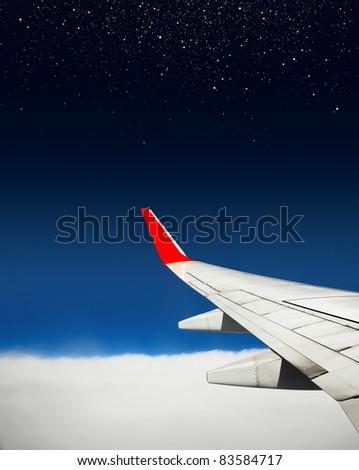 Aerial view from plane with wing and deep blue sky with white stars - stock photo