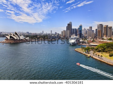Aerial view from Sydney Harbour bridge lookout at Circular quay with ferries and overseas passenger terminal in front of city CBD skyscrapers on a sunny summer day.