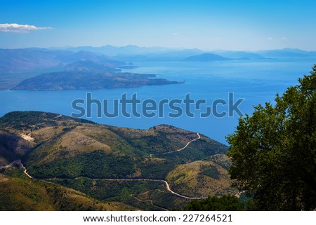 Aerial view from the Pantokrator peak and monastery to the sea and mainland mountains in the background from 917 m altitude at Corfu Island Greece - stock photo