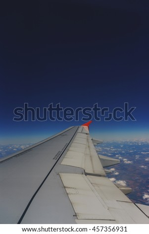 aerial view from the window of a passenger airliner in flight at the clouds. Clouds and landscape under the wing of the aircraft.