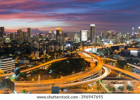 Aerial view highway interchanged with city downtown background at twilight, long exprosure