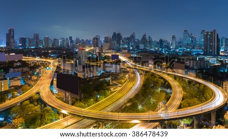 Aerial view highway road curved with city downtown background during twilight - stock photo
