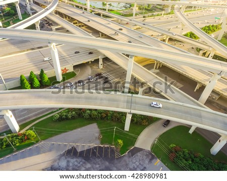 Aerial view massive highway intersection, stack interchange with elevated road junction overpass at late afternoon in Houston, Texas. This five-level freeway interchange carry heavy rush hour traffic. - stock photo