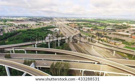 Aerial view massive highway intersection, stack interchange with elevated road junction overpass at early morning in Houston, Texas. This five-level freeway interchange carry heavy traffic, panorama. - stock photo