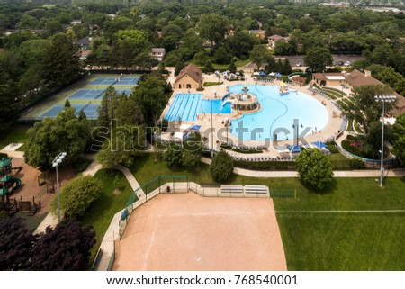Aerial view of a community swimming pool in a suburban setting with tennis courts and baseball diamond.