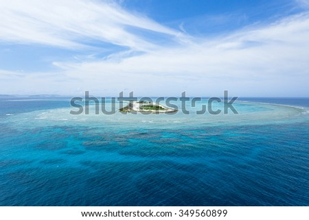 Aerial view of a deserted tropical island and coral reefs with clear blue water, Okinawa, Japan - stock photo