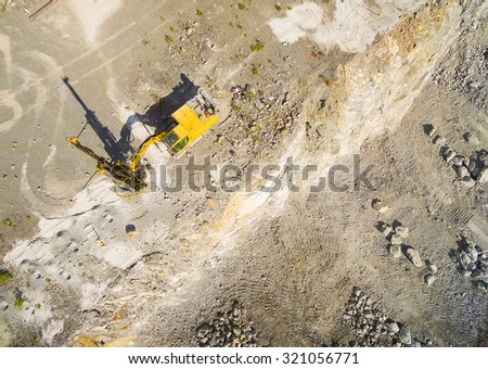 Aerial view of a drilling machine in the mine. Industrial background from landscape after mining. - stock photo