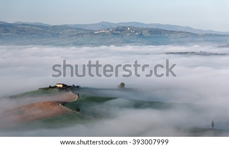Aerial view of a farmhouse on a foggy morning & a hilltop village in distant background ~ Amazing landscape of idyllic Tuscany countryside with rolling hills veiled in morning fog in Pienza, Italy - stock photo